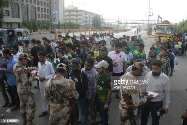 Pakistani paramilitary soldiers check match tickets from spectators before entering the National Cricket Stadium to watch the third and final...