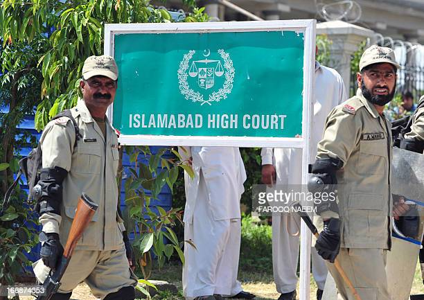 Pakistani paramilitary soldiers exit the high court after the case hearing of former military ruler Pervez Musharraf in Islamabad on April 18,2013. A...