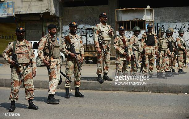Pakistani paramilitary soldiers stand guard after the funeral ceremony for members of Ahle Sunnat Wal Jamaat who were shot dead by unknown assailants...
