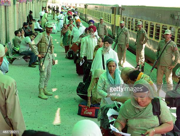 Pakistani paramilitary soldiers stand guard as Indian Sikh pilgrims arrive at Wagah Railway Station in Wagah on April 10 to celebrate Baisakhi or the...