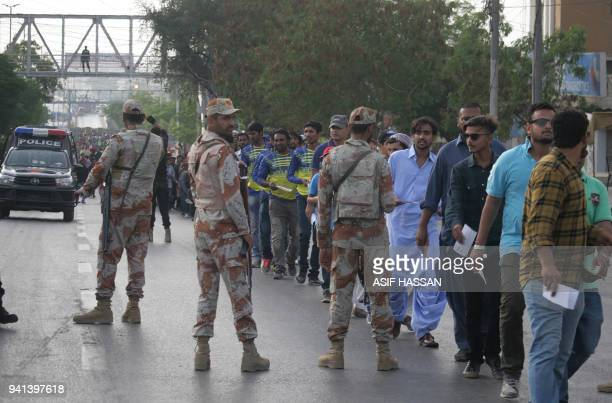 Pakistani paramilitary soldiers stand guard as spectators stand in a queue before entering the National Cricket Stadium to watch the third and final...