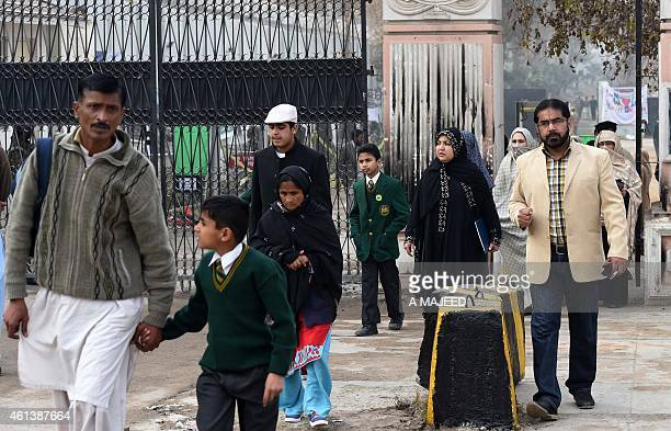 Pakistani parents leave the Army Public School with their children after it was reopened following an attack there by Taliban militants in Peshawar...