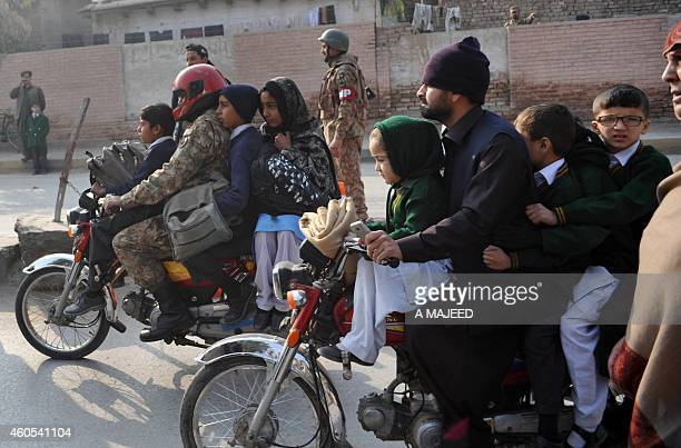 Pakistani parents leave with their children near the site of an attack by Taliban gunmen on a school in Peshawar on December 16 2014 Taliban...