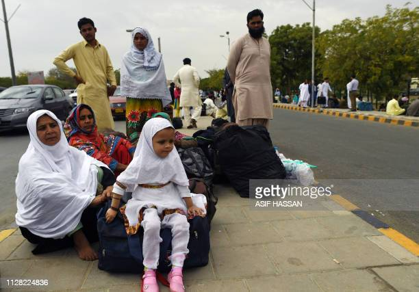 Pakistani passengers sit outside the Jinnah International Airport as they wait for flight operations to resume in Karachi on March 1 2019 Pakistan...