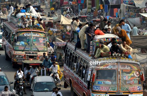Pakistani passengers travel on an overcrowded bus in Lahore on June 24 as they to go home to celebrate the Muslim festival of EidulFitr which marks...