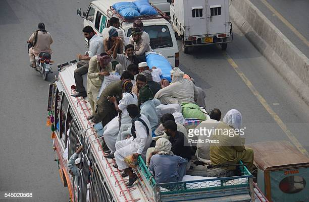 Pakistani passengers travel on the rooftop of a passenger bus as they travel to their home towns to celebrate the Eid with their loved ones ahead of...