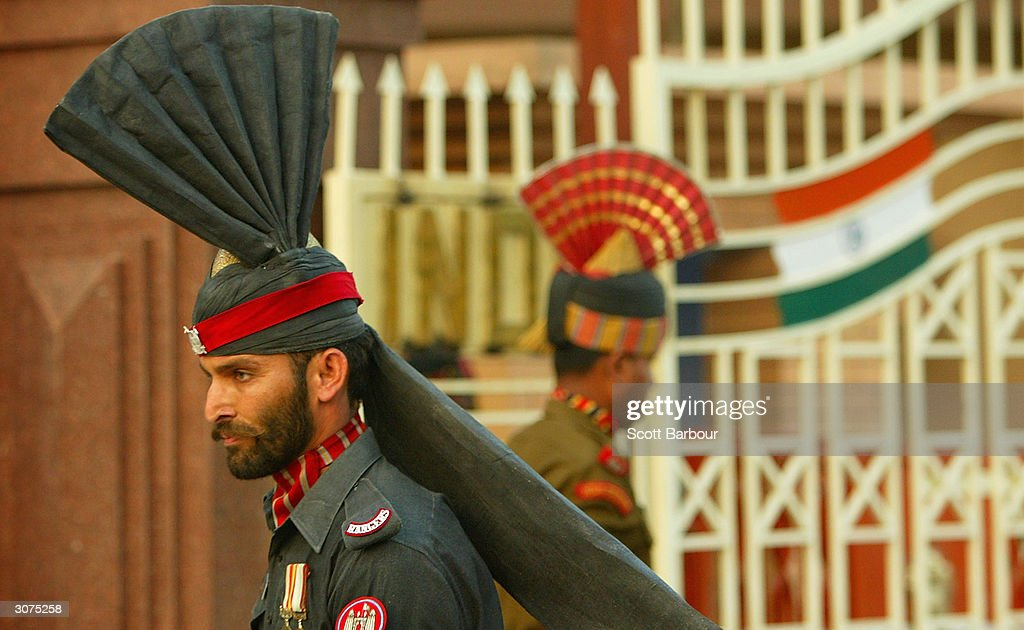Pakistani Patan guard and an Indian Border Security force officer march during the ceremony to lower the national flags at the border crossing...
