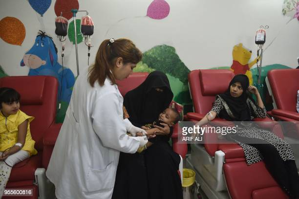 Pakistani patients suffering from thalassemia receive blood transfusion during treatment to mark the World Thalassemia Day in Lahore on May 7 2018...