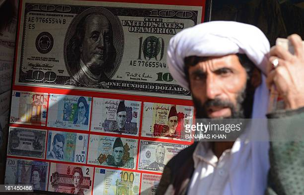 A Pakistani pedestrian walks past the currency exchange shop in Quetta on February 11 2013 The Pakistani rupee on Monday sank to an alltime low...