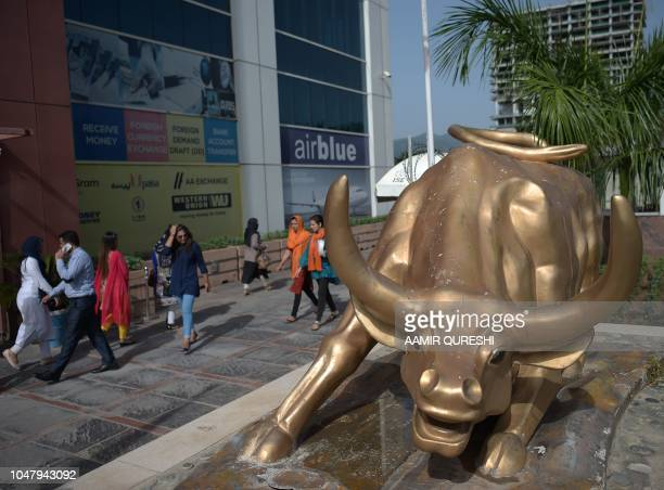Pakistani pedestrians walk past a bronze bull statue outside the Pakistan Stock Exchange building in Islamabad on October 9 2018 The International...