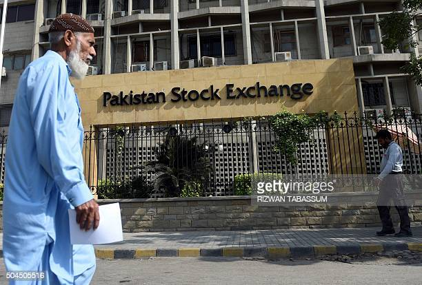 Pakistani pedestrians walk past the Pakistan Stock Exchange in Karachi on January 11 2016 The benchmark PSE100 index was down 3235443 in midday trade...