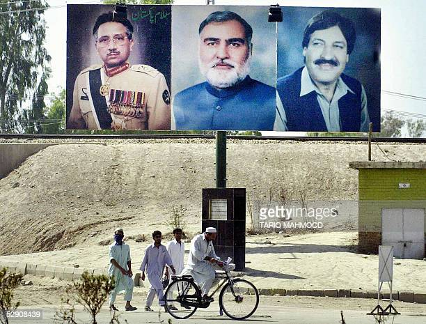 Pakistani pedestrians walk under a billboard which display the portraits of Pakistani President Pervez Musharraf province NWFP Chief Minister Akram...