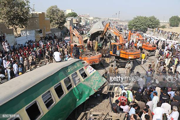 Pakistani people and rescue team members inspect the site of the train accident in Karachi on November 032016At least 17 people were killed and over...
