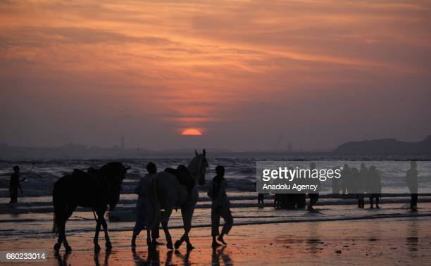 Pakistani people bathe in the sea to cool themselves during sunset at Clifton beach in Karachi Pakistan on March 29 2017