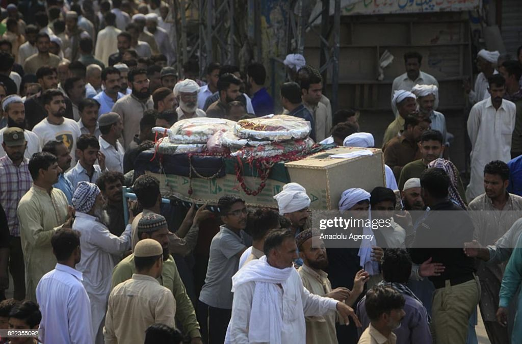Pakistani people carry a coffin of a blast victim during funeral ceremony after a suicide bomb attack in Lahore Pakistan on July 25 2017 An explosion.