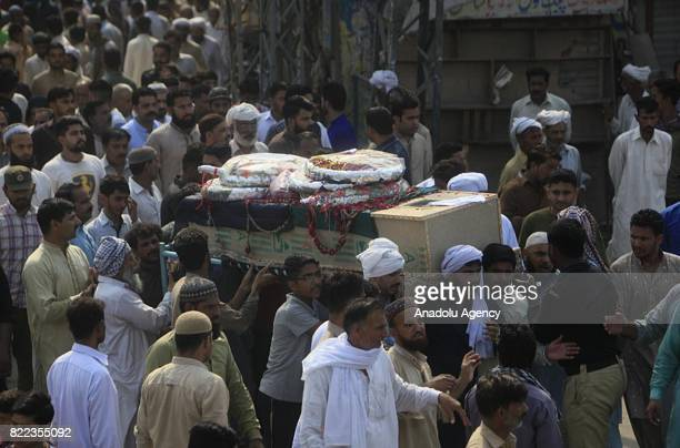 Pakistani people carry a coffin of a blast victim during funeral ceremony after a suicide bomb attack in Lahore Pakistan on July 25 2017 An explosion...