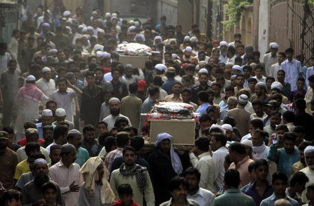 Pakistani people carry the coffins of blast victims during funeral ceremony after a suicide bomb attack in Lahore Pakistan on July 25 2017 An...