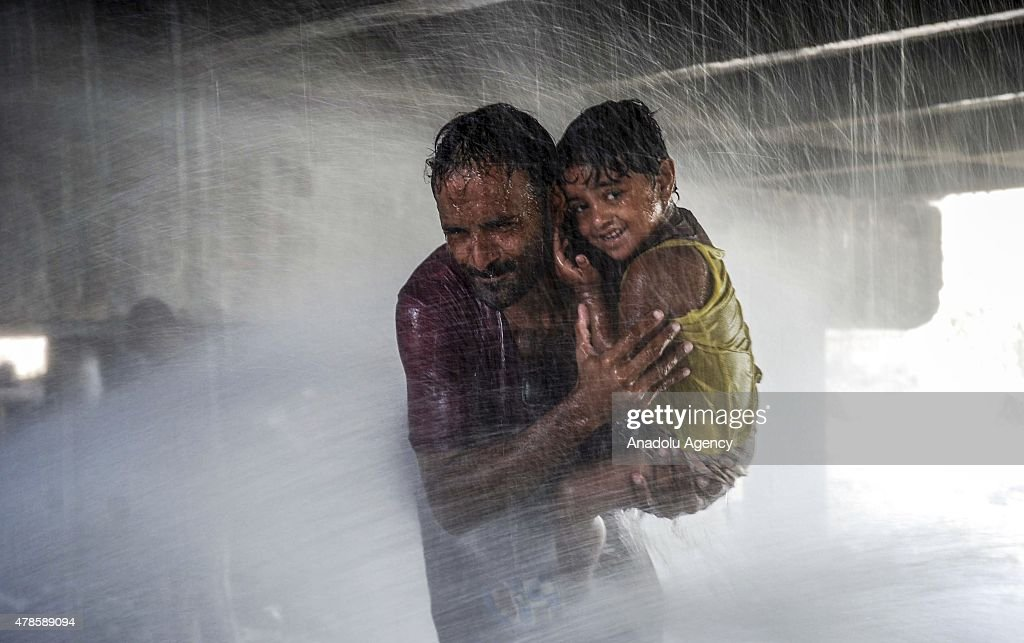 Pakistani people cool off at water supply pipelines during a heatwave in Karachi, Pakistan on June 26, 2015. More than 1,000 people have been killed over five days by a searing heatwave in Pakistan, with the worst effects in the country's commercial capital Karachi.