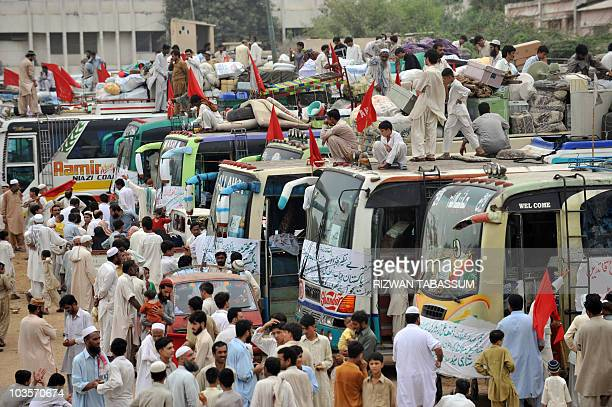 Pakistani people displaced by the military operation against the Taliban in Swat valley load their belongings onto buses to return home from a camp...