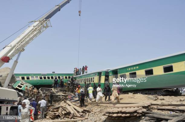 Pakistani people gather around a badly damaged passenger train at the site after a passenger train crashed into a freight train at Rahim Yar Khan...