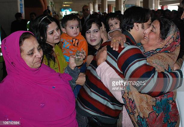 Pakistani people greet their relatives arriving from Libya at the Allama Iqbal International Airport in Lahore on March 3 2011 Tens of thousands of...
