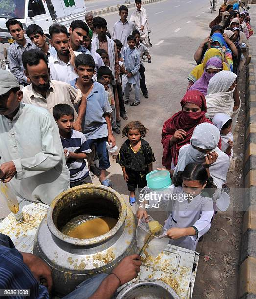 Pakistani people lineup to receive food donated by a welfare trust in Lahore on May 9 2009 The government has blamed the country's economic woes on...