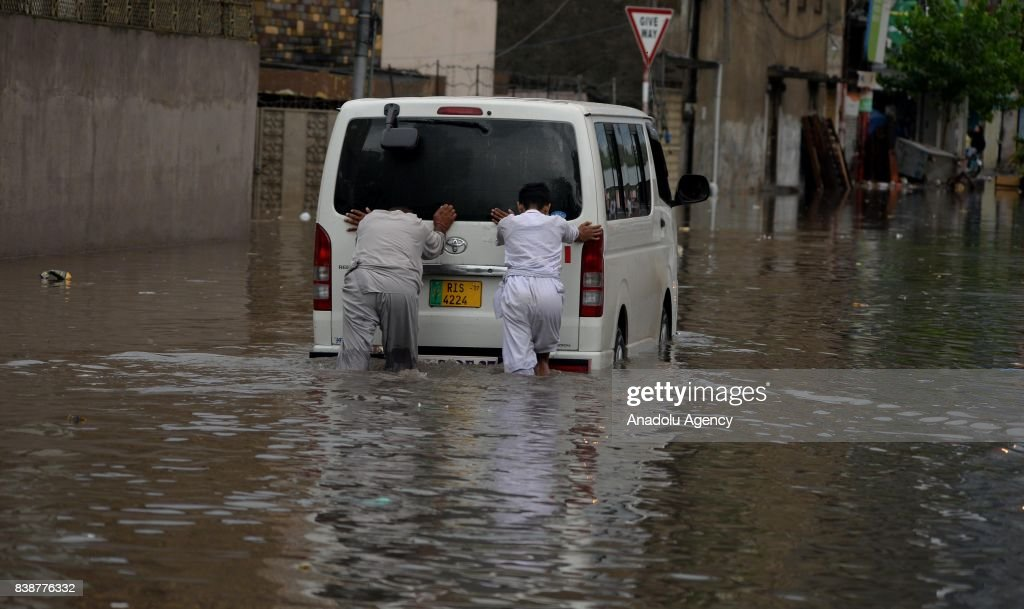 Pakistani people push a vehicle which was stuck in a flooded street after heavy monsoon rains hit the city of Rawalpindi Pakistan on August 25 2017...