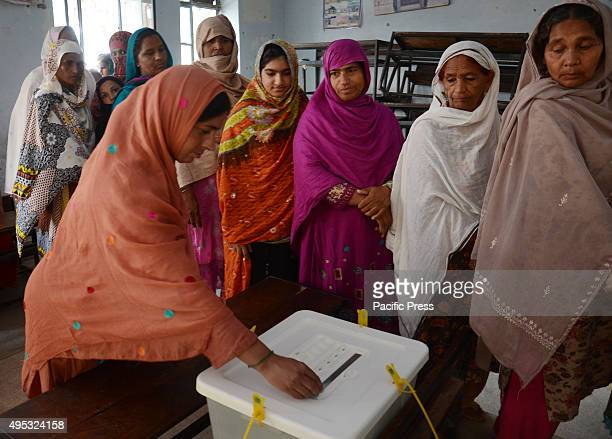 Pakistani people queue to cast their ballots at a polling station during the local government elections in Lahore Local election was held in eight...