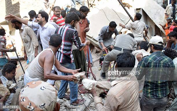 Pakistani people search for victims in the rubble of a building after an old structured building collapsed in Hyderabad Pakistan leaving at least 11...