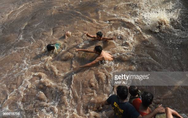 Pakistani people swim in a canal during a hot summer day in Lahore on June 3 2018