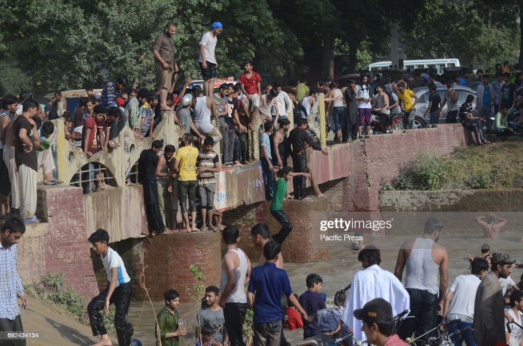 Pakistani people taking bath in the canal water to beat the heat and get some relief from the extremely hot weather during eighth day of the holy...
