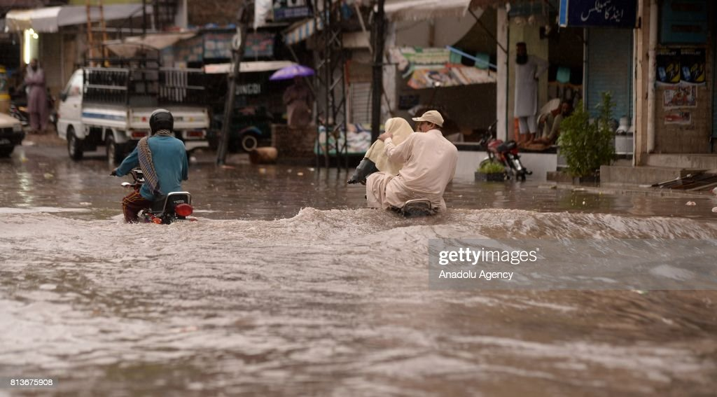 Pakistani people try to pass through a flooded street with their motorbikes after heavy monsoon rains hit Rawalpindi province of Pakistan on July 13..