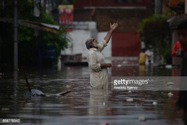 Pakistani people wade through a flooded street after heavy monsoon rains hit the city of Rawalpindi Pakistan on August 25 2017 Heavy monsoon rains...
