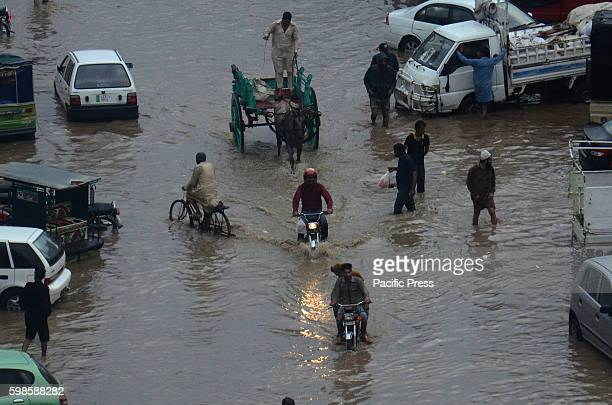 Pakistani people wade through floodwaters during heavy monsoon rain fall in Lahore Heavy monsoon rain disrupted life in Lahore and triggered flooding...