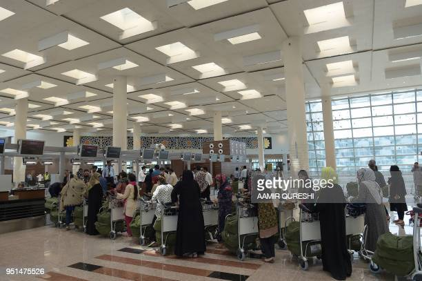 Pakistani people wait in queue to get boarding pass at an international counter during a rehearsal by the airport officials at the newly built...