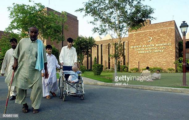 Pakistani people walk infront of the entrance to the Shaukat Khanum Memorial Cancer Hospital and Research Centre founded by former Pakistani cricket...