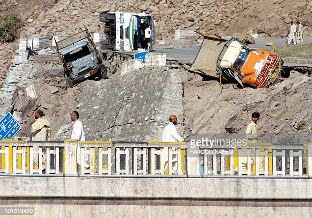 Pakistani people walk past overturned vehicles in Balakot in the North West Frontier Province 09 October 2005 a day after a massive 76 magnitude...