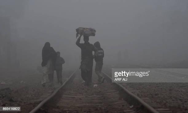 A Pakistani people walk through dense fog across railway tracks on the outskirts of Lahore on December 15 2017 / AFP PHOTO / ARIF ALI