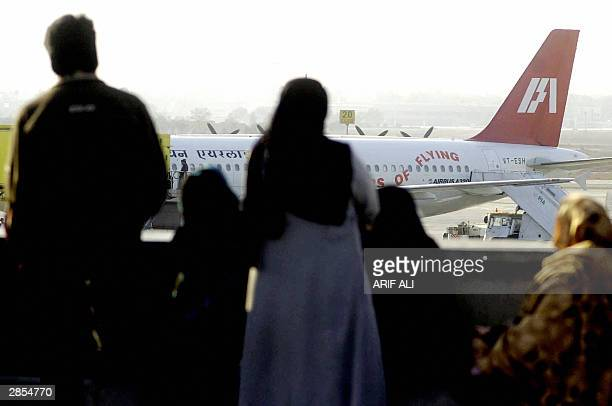 Pakistani people watch the first Indian Airlines jet to arrive in Pakistan since the resumption of flight links between India and Pakistan after it...