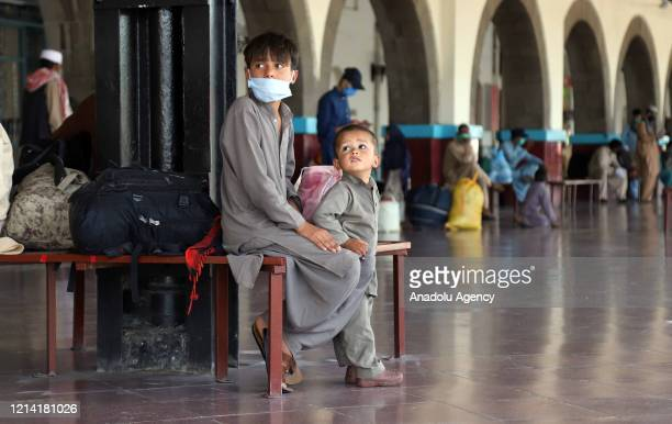 Pakistani people wearing a face mask as a precaution against coronavirus are seen at Rawalpindi Railways Station as they leave for their hometowns to...