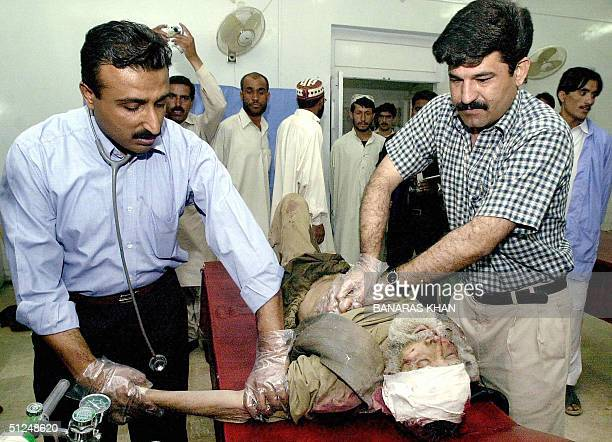 Pakistani peramedics give medical assistance to a man who was injured in a bomb blast which ripped through a sweet shop in Baluchistan province's...