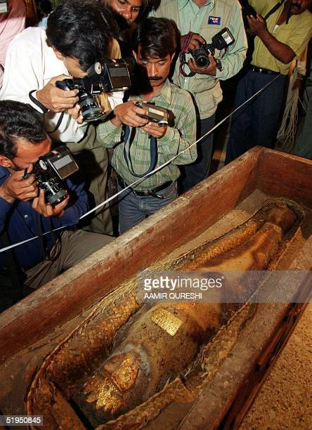 Pakistani photographers hover over an ancient mummy show for the first time during a press conference at the National Museum in Karachi 26 October...