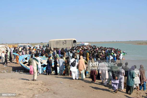 Pakistani pilgrims gather on the shore as a rescue operation continues a day after two passenger boats collided in the sea in Thatta on December 8...