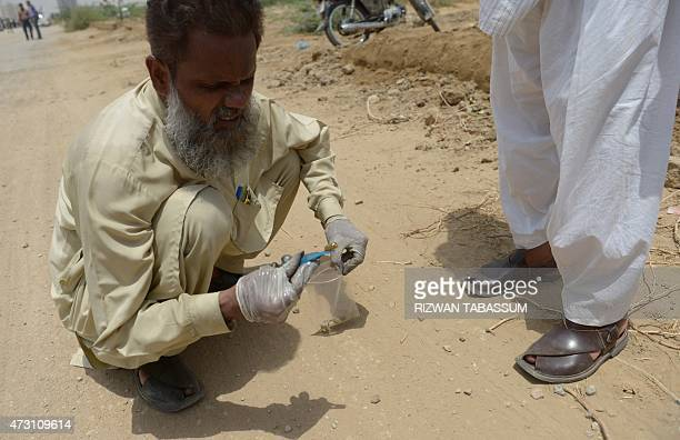 A Pakistani plainclothes police official collects evidence at the scene of an attack by gunmen on a bus carrying Shiite Muslims in Karachi on May 13...