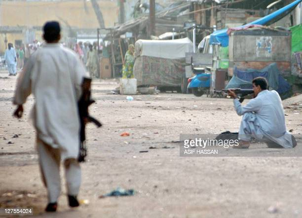 A Pakistani plainclothes policeman aims with his AK47 Kalashnikov to protesters during a riot which erupted during a protest to condemn the killing...