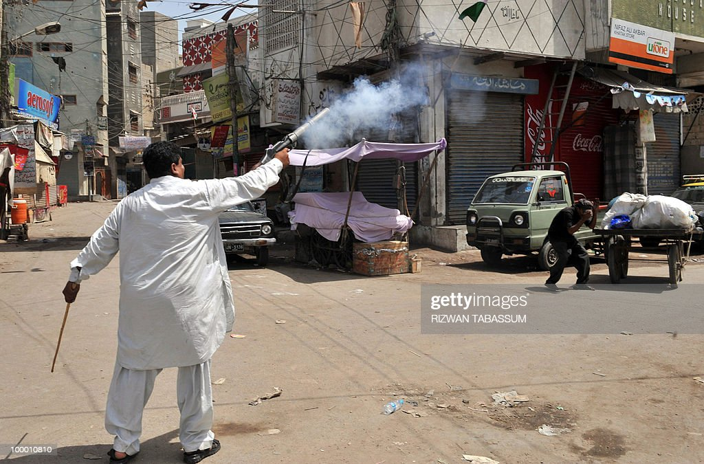 A Pakistani plain-clothes policeman fires a tear gas shell towards demonstrators during a protest against alleged target killings in Karachi on May 20, 2010. At least 17 people including two children have been killed in political clashes in Pakistan's financial capital Karachi in the past two days, a government official and police said. Police and paramilitary have been put on high alert and authorities closed all schools and colleges after the latest outbreak of politically related violence in Karachi, the biggest and richest city in Pakistan.