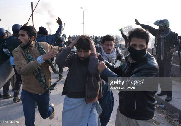 Pakistani plainclothes policemen arrest an injured activist from the TehreekiLabaik Yah Rasool Allah Pakistan religious group during a clash in...