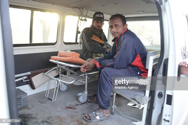 Pakistani police and a man are seen in an bloodstained ambulance outside the Balochistan Police Training College in Quetta on October 24 after...