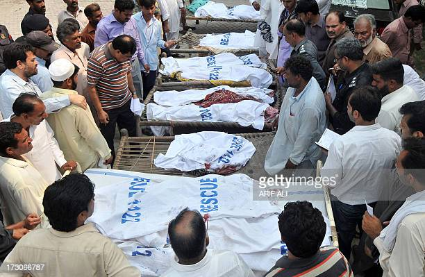 Pakistani police and media officials gather around the bodies of train accident victims in Khanpur town of district Sheikhupura around 40 kilometres...