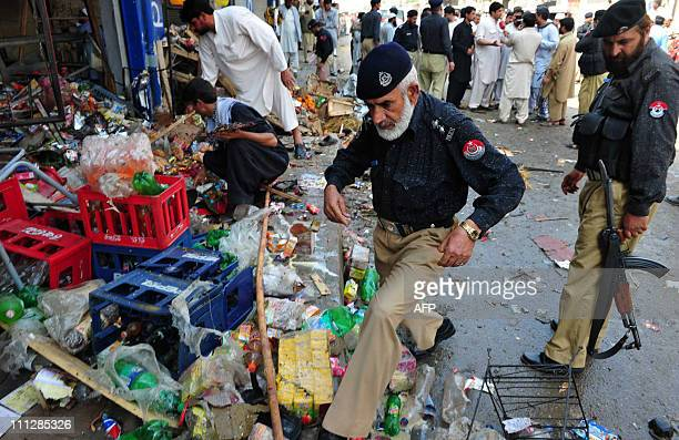 Pakistani police and shops owners examine the site of a bomb blast in the town of Charsadda on March 31 2011 A bomb blast targeting an Islamic party...